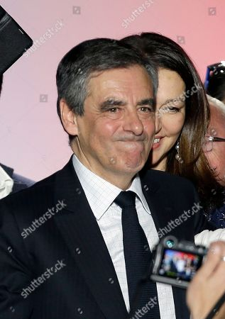 French conservative presidential candidate Francois Fillon grimaces, with Valerie Boyer behind, during a campaign meeting in Marseille, southern France, Tuesday, April, 11, 2017. The two-round presidential election is set for April 23 and May 7