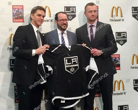 Stock Image of Luc Robitaille, Dan Beckerman, Rob Blake Los Angeles Kings president Luc Robitaille, left, holds up a team jersey with Anschutz Entertainment Group CEO Dan Beckerman, middle, and Kings general manager Rob Blake after a news conference, in Los Angeles, Calif. Robitaille and Blake were promoted by the Kings after the firing of general manager Dean Lombardi and coach Darryl Sutter