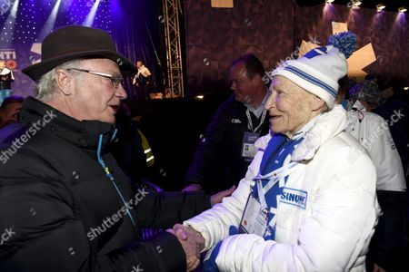 King of Sweden Carl Gustav shakes hands with Finnish ski legend Siiri Rantanen at the medals ceremony for ladies 4 x 5km relay competition