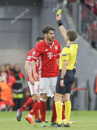 Bayern's Javi Martinez (L) receives the yellow card from Referee Nicola Rizzoli during the UEFA Champions League quarter final, first leg soccer match between Bayern Munich and Real Madrid at Allianz Arena in Munich, Germany, 12 April 2017.