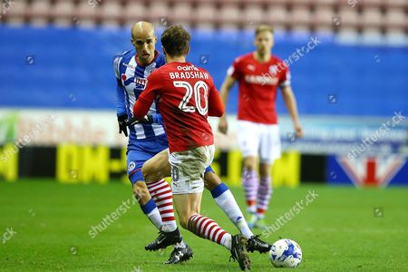 Stock Image of Gabriel Obertan is tackled by Tom Bradshaw during the SKY BET Championship match between Wigan Athletic and Barnsley played at the DW Stadium, Wigan on 13th April, 2017