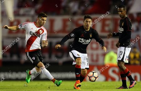 Jean Barrientos of Peru's Melgar, center, tries to control the ball next to his teammate Nilson Loyola, right, and Lucas Alario of Argentina's River Plate, left, during a Copa Libertadores soccer match in Buenos Aires, Argentina