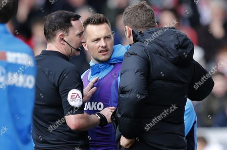 Ref Joe Johnson speaks to Torquay United's Shaun Harrad on the touchline - who is shown a yellow card during the Vanarama National League Match between Lincoln City and Torquay United at Sincil Bank, Lincoln on April 14.