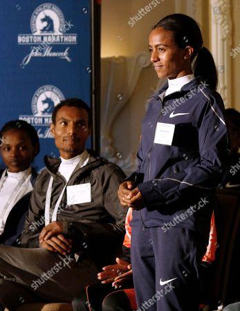 Stock Image of Atsede Baysa, Lemi Berhanu Hayle, Buzunesh Deba Top-seeded distance runners Atsede Baysa, left, and Lemi Berhanu Hayle, center, watch Buzunesh Deba, all of Ethiopia, stand during a Boston Marathon media availability, in advance of Monday's race in Boston. In 2016, Deba was named the 2014 Boston Marathon winner following the disqualification of Rita Jeptoo, of Kenya, for doping