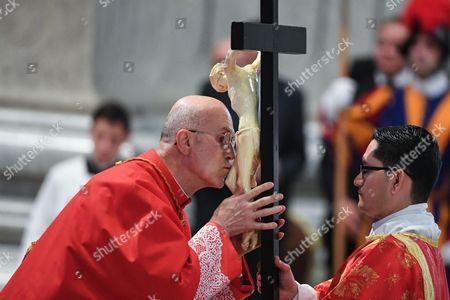 Cardinal Tarcisio Bertone kisses a crucifix during the celebration of the Passion of Christ on Good Friday at Saint Peter's Basilica, Vatican City, in Rome, 14 April 2017.