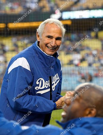 Sandy Koufax, Magic Johnson Former Los Angeles Dodgers pitcher Sandy Koufax, top, sits in the stands with Dodgers co-owner Magic Johnson prior to the team's baseball game against the Arizona Diamondbacks, in Los Angeles