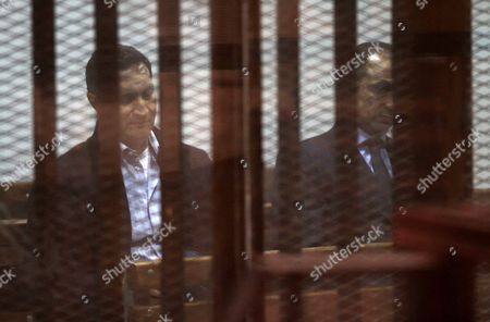 Stock Photo of Alaa and Gamal Mubarak, the sons of former president Hosni Mubarak sit in a courtroom cage during their trial in ''Stock Market Manipulation'' case, in Cairo, Egypt