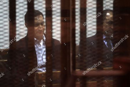 Alaa and Gamal Mubarak, the sons of former president Hosni Mubarak sit in a courtroom cage during their trial in ''Stock Market Manipulation'' case, in Cairo, Egypt