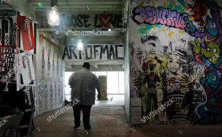 "Stock Photo of Sean Sullivan, who goes by the moniker ""Layer Cake,"" leaves after making last minute enhancements to his graffiti-style artwork, right, on a wall inside the unoccupied 69th floor of 4 World Trade Center, in New York. Sullivan's father was a detective with the city police bomb squad who lost his best friend on 9/11 and was himself hurt in the attack. Sullivan includes a figure in a bomb suit to represent his father. He is among a group of artists offered free use of 34,000 square feet of office space that normally would rent for about quarter of a million dollars a month"