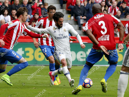 Real Madrid's midfielder Isco Alarcon (C) vies for the ball with Sporting de Gijon's Fernando Amorebieta (L) and Jean-Sylvain Babin (R) to score during their Spanish Primera Division league game at El Molinon Stadium in Gijon, northern Spain, 15 April 2017.