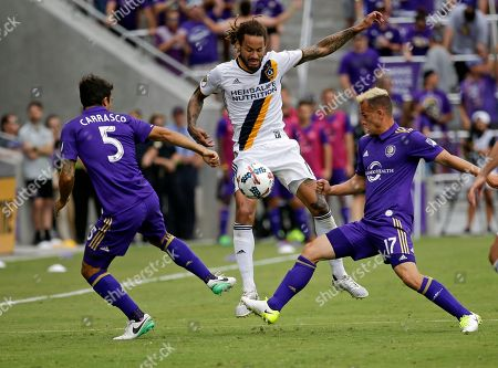 Servando Carrasco, Jermaine Jones, Luis Gil Los Angeles Galaxy's Jermaine Jones, center, moves the ball between Orlando City's Servando Carrasco (5) and Luis Gil (17) during the second half of an MLS soccer game, in Orlando, Fla. Orlando won 2-1