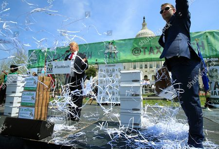 Shredded papers are thrown symbolizing shredded tax returns, while Anthony Atamanuik of Comedy Central, left, impersonating President Donald Trump, speaks during a Tax Day demonstration on Capitol Hill in Washington, calling on President Donald Trump to release his tax returns