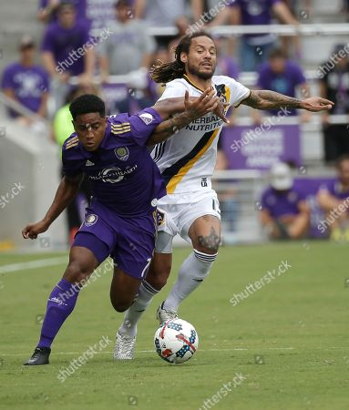 Orlando City's Cristian Higuita, left, and Los Angeles Galaxy's Jermaine Jones battle for possession of the ball during the first half of an MLS soccer game, in Orlando, Fla