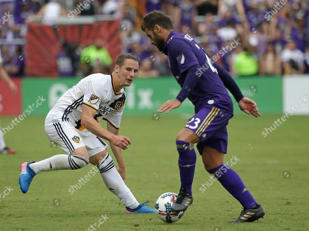Los Angeles Galaxy's Nathan Smith, left, looks to stop Orlando City's Antonio Nocerino, right, during the second half of an MLS soccer game, in Orlando, Fla. Orlando won 2-1