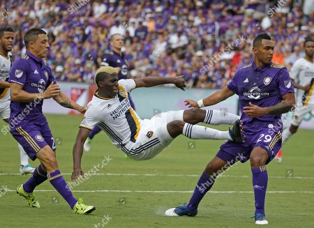 Los Angeles Galaxy's Gyasi Zerdes, center, goes airborne after taking a shot on goal between Orlando City's Jonathan Spector, left, and Tommy Redding (29) during the second half of an MLS soccer game, in Orlando, Fla. Orlando won 2-1