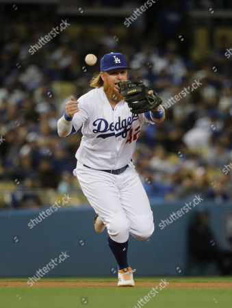 Los Angeles Dodgers' Justin Turner makes a fielding error while trying to catch a ball hit by Arizona Diamondbacks' Jeremy Hazelbaker during the fifth inning of a baseball game, in Los Angeles