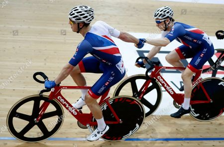 Great Britain's Mark Stewart and Oliver Wood tag during the men's madison final at the World Track Cycling championships in Hong Kong