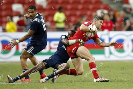 Justin Douglas (R) of Canada is tackled by Perry Baker (C) of the USA during the final match of the HSBC 7s World Rugby Series tournament held at the National Stadium in Singapore, 16 April 2017.