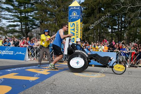 Denna Laing, Bobby Carpenter, Dave McGillivray Bobby Carpenter, gets a high-five from race director Dave McGillivray as he crosses the start line pushing Denna Laing at the start of the 2017 Boston Marathon in Hopkinton, Mass., . Carpenter was the first American-born player to be taken in the first round of an NHL Draft. Laing has been wheelchair-bound since being injured in the 2015 Women's Winter Classic