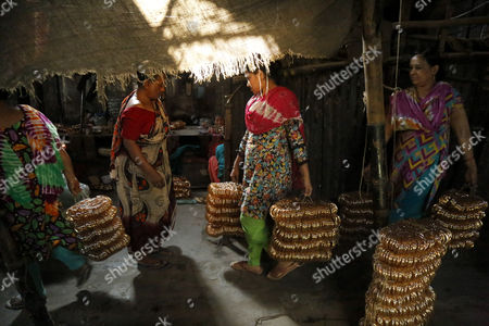 A group of women carry bangles for the final process inside a factory where they work without safety measures at Kamrangirchar in Dhaka, Bangladesh 17 April 2017. The women workers use fire from the gas to heat and join the bangles maually. They earn 50 euro (53 US dollar) per month working more than 12 hours per day. Colorful bangles are a traditional ornament popular to South Asian women including Bangladesh, Pakistan, and India.