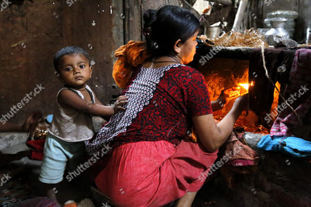 A woman works in a bangle factory without safety measures while her child looks on at Kamrangirchar in Dhaka, Bangladesh 17 April 2017. The women workers use fire from the gas to heat and join the bangles maually. They earn 50 euro (53 US dollar) per month working more than 12 hours per day. Colorful bangles are a traditional ornament popular to South Asian women including Bangladesh, Pakistan, and India.