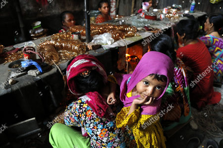A child of a woman worker looks on in a bangle factory where they work without safety measures at Kamrangirchar in Dhaka, Bangladesh 17 April 2017. The women workers use fire from the gas to heat and join the bangles maually. They earn 50 euro (53 US dollar) per month working more than 12 hours per day. Colorful bangles are a traditional ornament popular to South Asian women including Bangladesh, Pakistan, and India.