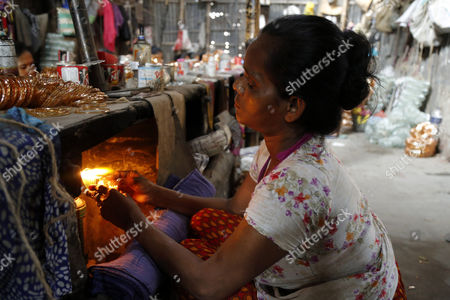 A woman works in a bangle factory without safety measures at Kamrangirchar in Dhaka, Bangladesh 17 April 2017. The women workers use fire from the gas to heat and join the bangles maually. They earn 50 euro (53 US dollar) per month working more than 12 hours per day. Colorful bangles are a traditional ornament popular to South Asian women including Bangladesh, Pakistan, and India.
