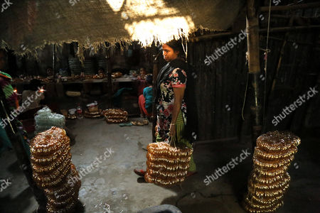 A woman carries bangles for the final process inside a factory where they work without safety measures at Kamrangirchar in Dhaka, Bangladesh 17 April 2017. The women workers use fire from the gas to heat and join the bangles maually. They earn 50 euro (53 US dollar) per month working more than 12 hours per day. Colorful bangles are a traditional ornament popular to South Asian women including Bangladesh, Pakistan, and India.