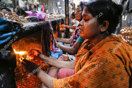 A group of women work in a bangle factory without safety measures at Kamrangirchar in Dhaka, Bangladesh 17 April 2017. The women workers use fire from the gas to heat and join the bangles maually. They earn 50 euro (53 US dollar) per month working more than 12 hours per day. Colorful bangles are a traditional ornament popular to South Asian women including Bangladesh, Pakistan, and India.