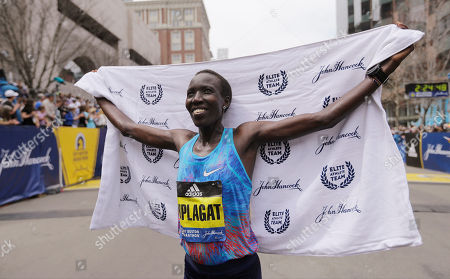 Edna Kiplagat, of Kenya, poses for photographers after winning the women's division of the 121st Boston Marathon, in Boston
