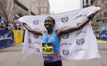 Edna Kiplagat, of Kenya, poses for photographers after winning the women's division of the 121st Boston Marathon, in Boston