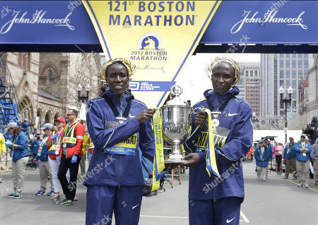 Edna Kiplagat, left, and Geoffrey Kirui, both of Kenya, hold a trophy together after their victories in the 121st Boston Marathon, in Boston