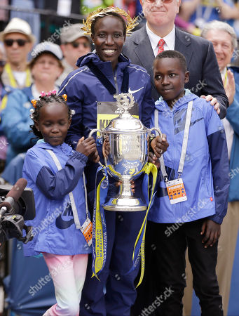 Edna Kiplagat, winner of the women's division, holds a trophy with her children Wendy Jemutai, 9, and Carlos Kipkorir, 13 after her victory in the 121st Boston Marathon, in Boston