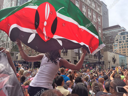 Sally Thitu, 25, originally from Kenya, waves the flag while watching the 121st Boston Marathon, in Boston. Kenyans Edna Kiplagat and Geoffrey Kirui won the women's and men's divisions in the race