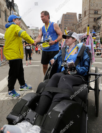 Stock Image of Boston Marathon race director Dave McGillivray, left, congratulates Bobby Carpenter, center, who pushed Denna Laing, right, in the the 121st Boston Marathon, in Boston. Carpenter was the first American-born player to be taken in the first round of an NHL Draft. Laing has been wheelchair-bound since being injured in the 2015 Women's Winter Classic