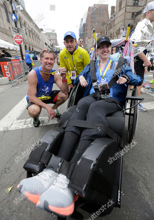 Bobby Carpenter, left, poses with Boston Marathon race director Dave McGillivray and Denna Laing, right, after he pushed Laing in the the 121st Boston Marathon, in Boston. Carpenter was the first American-born player to be taken in the first round of an NHL Draft. Laing has been wheelchair-bound since being injured in the 2015 Women's Winter Classic