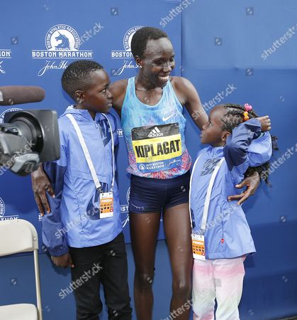 Edna Kiplagat of Kenya (C) celebrates with her children Wendy (R) and Carlos (L) after she crossed the finish line to win the women's division of the 121st Boston Marathon