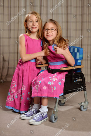 Seven Year Old Disabled Girl Rebecca Carey (glasses) Pictured With Her Twin Sister Charlotte At Their Home In Congleton Cheshire. Rebecca Needs Selective Dorsal Rhizotomy (sdr) Surgery In The Usa To Walk Again And Is Appealing To Dm Readers For Help.