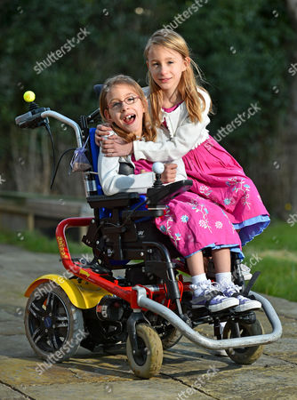 Editorial photo of Seven Year Old Disabled Girl Rebecca Carey (glasses) Pictured With Her Twin Sister Charlotte At Their Home In Congleton Cheshire. Rebecca Needs Selective Dorsal Rhizotomy (sdr) Surgery In The Usa To Walk Again And Is Appealing To Dm Readers For Help.