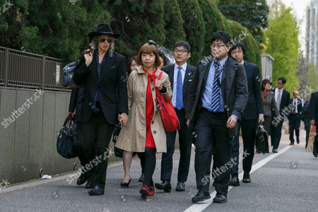 Japanese artist Megumi Igarashi (C) holds her fiance's hand Mike Scott of The Waterboys (L) upon her arrival at the Tokyo District Court, Tokyo, Japan.