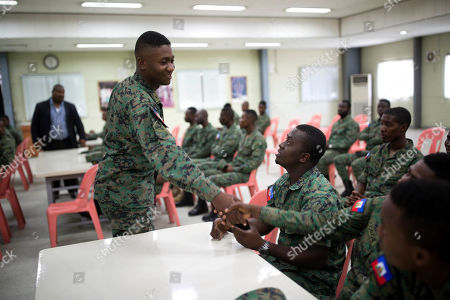 Stock Photo of A member of Haiti's new national military force greets a fellow soldier in a meeting room at a former U.N. base in Gressier, Haiti. Reviving a national army has been a goal of the Tet Kale party since it gained power in 2011. From his start as a candidate in 2010 elections, Michel Martelly pledged to restore the armed forces, pitching a force of 3,500 troops