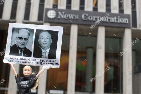 """Activist Judah Friedlander holds his """"Activist Barbie"""" with a photo of Bill O'Reilly, right, next to politician Bull Connor, who strongly opposed activities of the American Civil Rights Movement in the 1960s, in front of the News Corp. headquarters in Midtown Manhattan, . O'Reilly has lost his job at Fox News Channel after allegations that he sexually harassed women"""