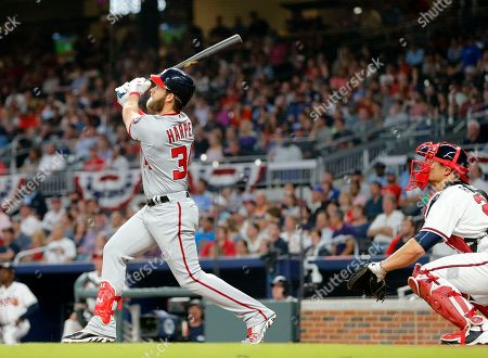 Stock Photo of Bryce Harper, Anthony Recker Washington Nationals right fielder Bryce Harper (34) watches the flight of a ball he hit for a grand-slam home run as Atlanta Braves catcher Anthony Recker (20) looks on in the second inning of a baseball game, in Atlanta. It was Harper's second of the game