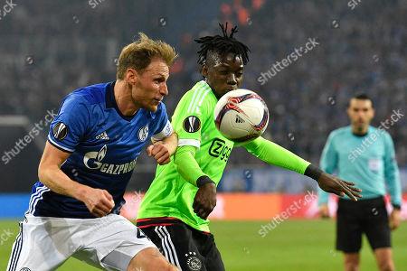 Schalke's Benedikt Howedes, left, and Ajax's Bertrand Traore challenge for the ball during the Europa League quarterfinal second leg soccer match between FC Schalke 04 and Ajax Amsterdam in Gelsenkirchen, Germany