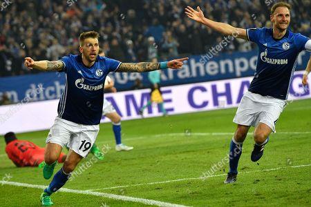 Schalke's Guido Burgstaller, left, celebrates with team mate Benedikt Howedes after scoring his side's second goal during the Europa League quarterfinal second leg soccer match between FC Schalke 04 and Ajax Amsterdam in Gelsenkirchen, Germany