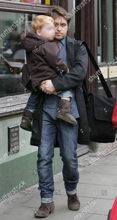 Mark Owen carrying son, Elwood Jack as they leave the Electric restaurant