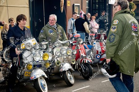 Mike Read (1st l) on a scooter with fans