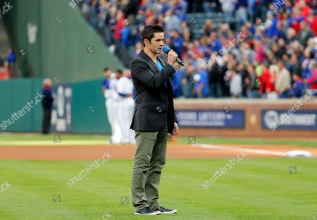Stock Photo of Singer Tim Urban of American Idol fame sings the national anthem before a baseball game between the Kansas City Royals and Texas Rangers in Arlington, Texas