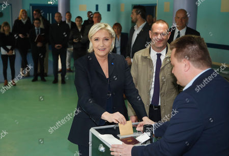 Far-right leader and candidate for the 2017 French presidential election Marine Le Pen casts her vote for the first-round presidential election while National Front Henin-Beaumont's mayor Steeve Briois, second right, looks, in Henin-Beaumont, northern France, . French voters are casting ballots for their next president in an unusually close first-round election Sunday, after a campaign dominated by concerns about jobs and immigration and clouded by security fears following a recent attack on police guarding the Champs-Elysees in Paris