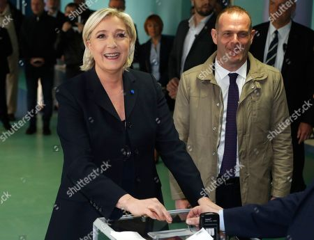 Far-right leader and candidate for the 2017 French presidential election Marine Le Pen casts her vote for the first-round presidential election while National Front Henin-Beaumont's mayor Steeve Briois, right, looks, in Henin-Beaumont, northern France, . French voters are casting ballots for their next president in an unusually close first-round election Sunday, after a campaign dominated by concerns about jobs and immigration and clouded by security fears following a recent attack on police guarding the Champs-Elysees in Paris